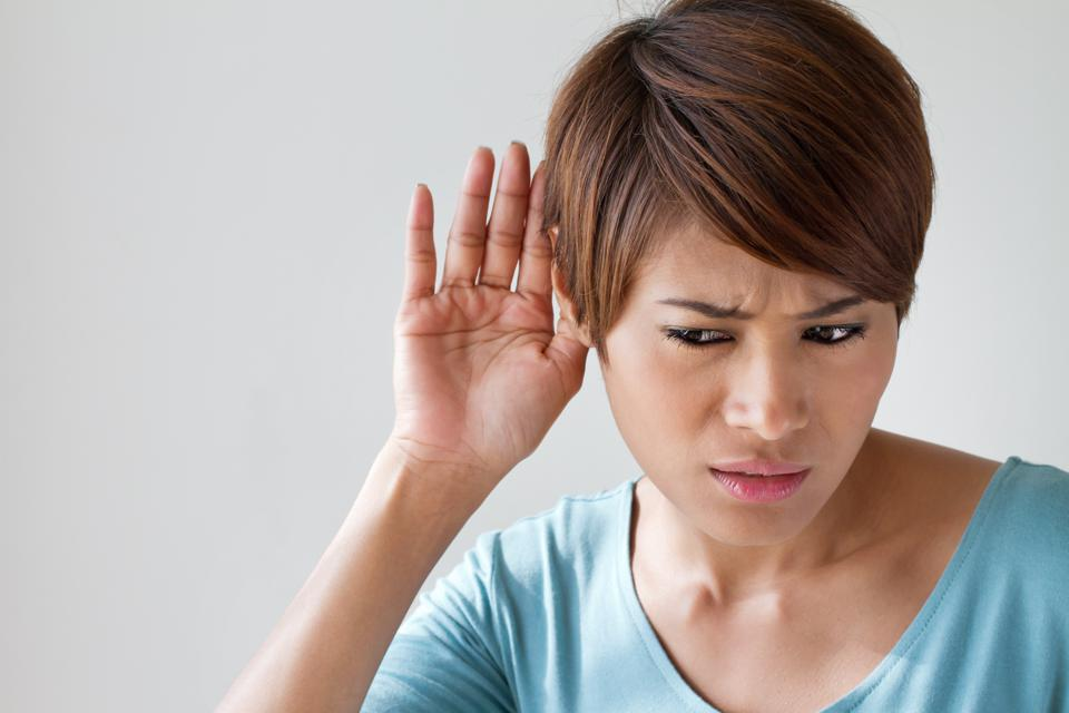 woman suffers from auditory impairment, hard of hearing