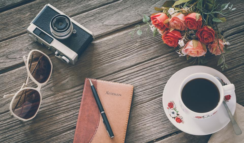 Vintage Film Look: cup of coffee with camera and notebook
