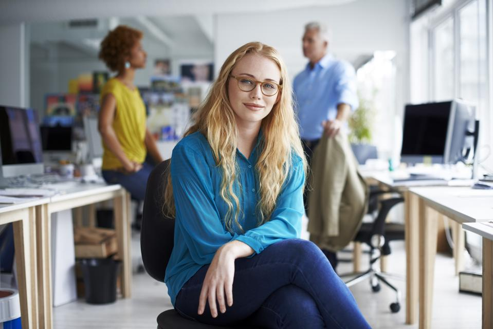 Smiling businesswoman sitting at creative office