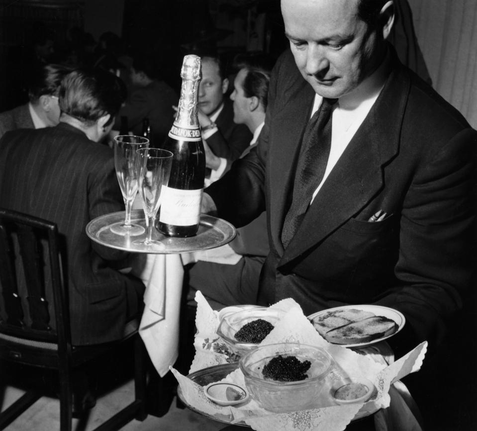 Waiter Holds Platters of Caviar and Champagne