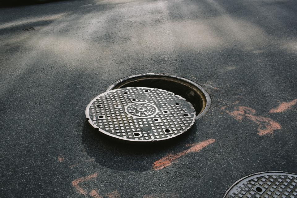 A manhole cover partially removed, close-up