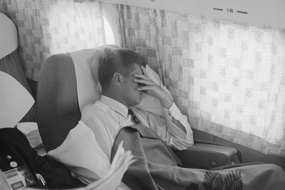 John F. Kennedy Resting in Passenger Cabin of Airplane