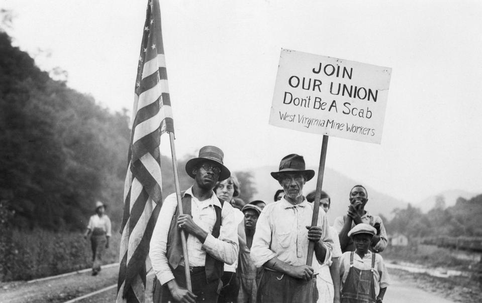 Striking Miners Hold Sign & Us Flag