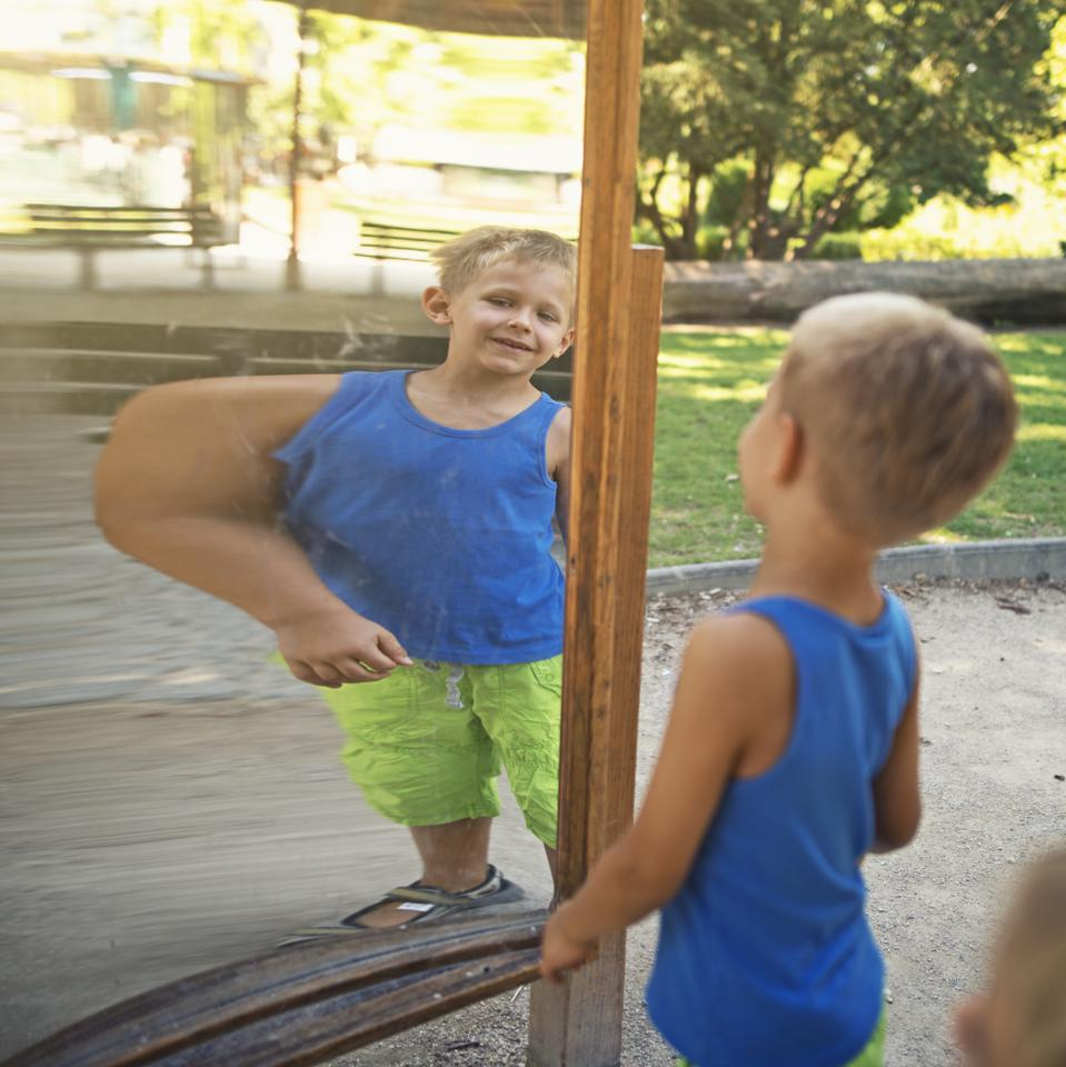 Little boy checking his muscles in funny distorting mirror