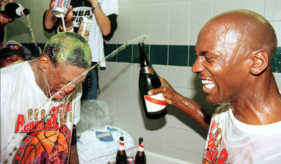 Dennis Rodman (L) of the Chicago Bulls gets beer a