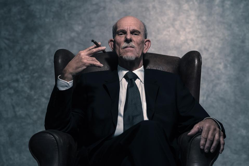 Cigar smoking senior businessman with gray beard wearing dark suit.