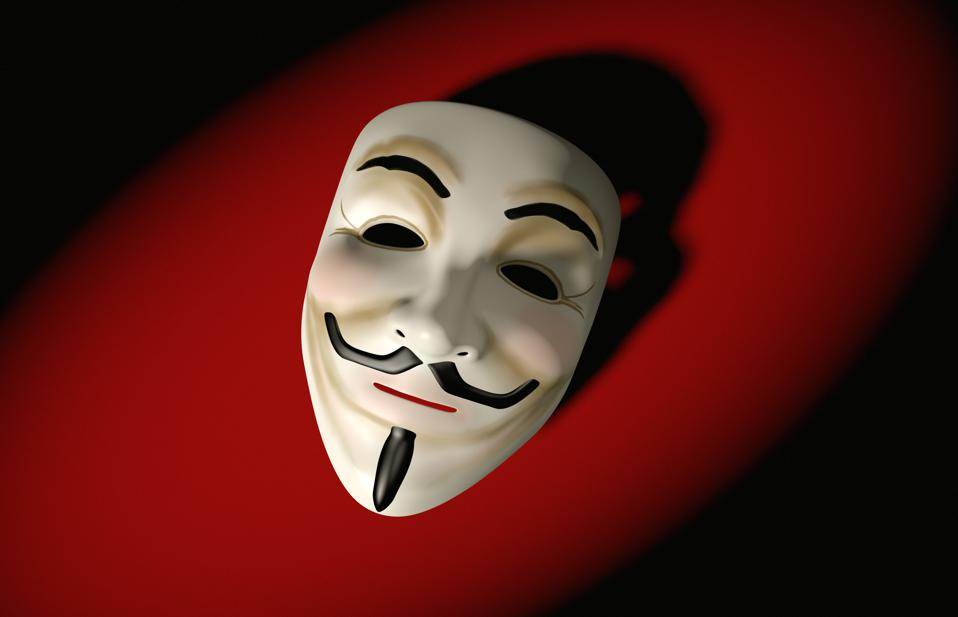 Mask of Guy Fawkes, as associated with the Anonymous hacktivist collective, against a red background