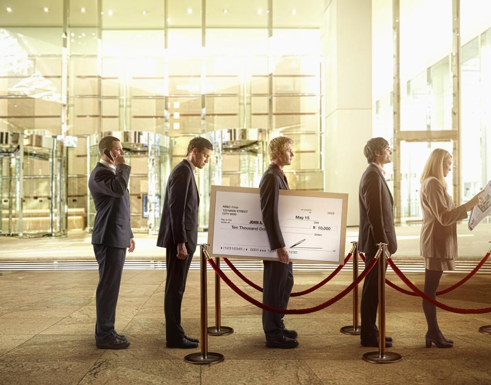 Businessman holding large check in bank line