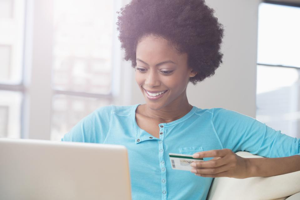 African American woman shopping on laptop with credit card on sofa