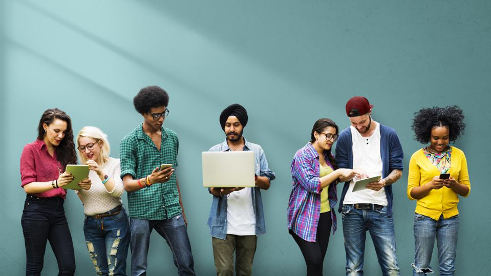 A diverse group of millennial men and women using laptops, smartphones and tablets.