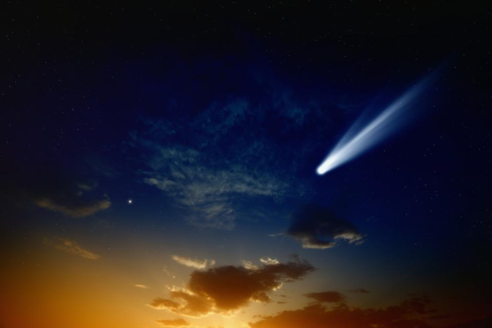 An illustration of a bright comet close to a sunset.