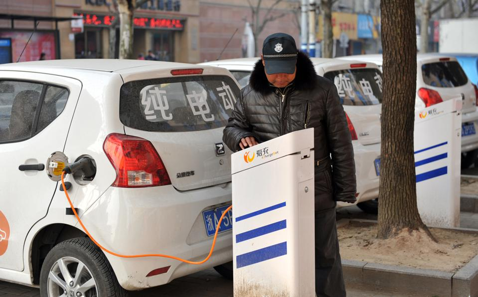 A driver charging an electric vehicle in China.