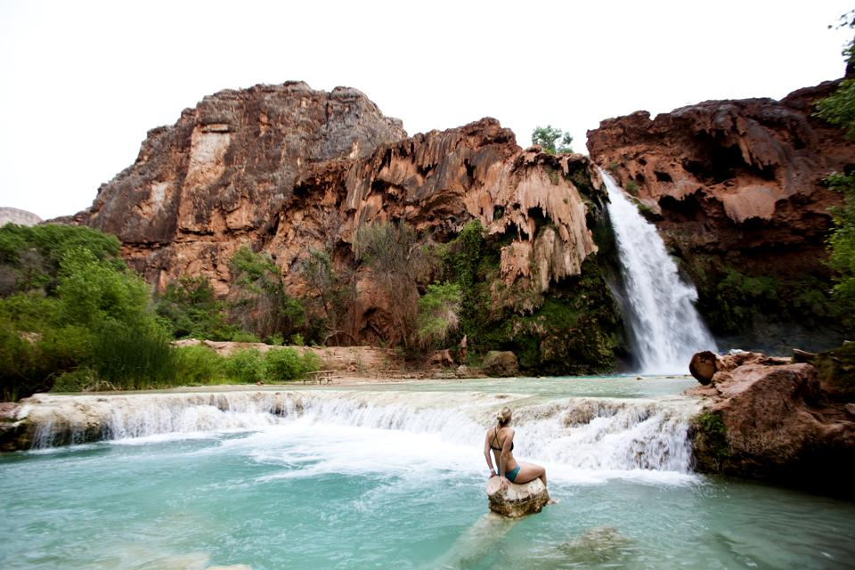 Woman sitting on stone by Havasupai Falls near Grand Canyon National, Arizona, USA