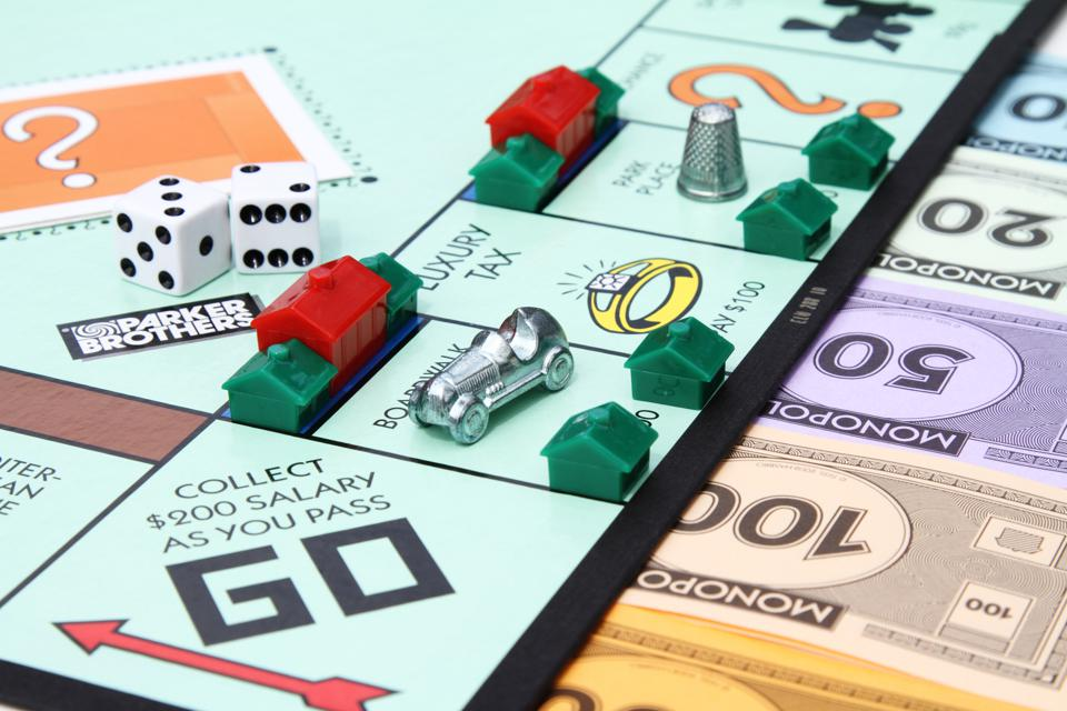A partial view of a Monopoly game board showing the Go start square with various game playing pieces set up on the board.  Game pieces visible include dice, hotel and house property pieces, game currency and the Race Car and Thimble game tokens.