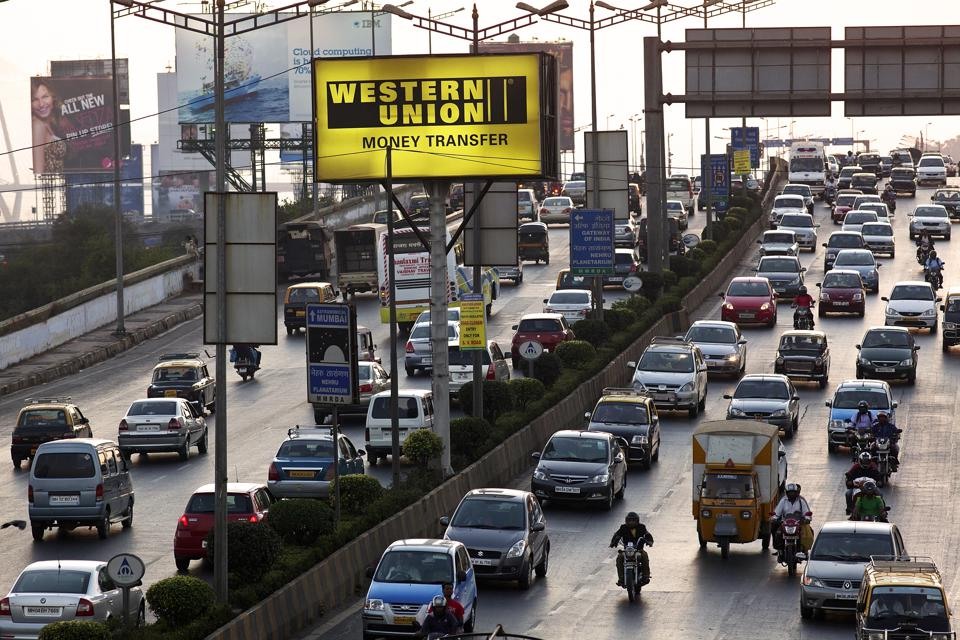 A crowded highway in Mumbai, India with a Western Union sign