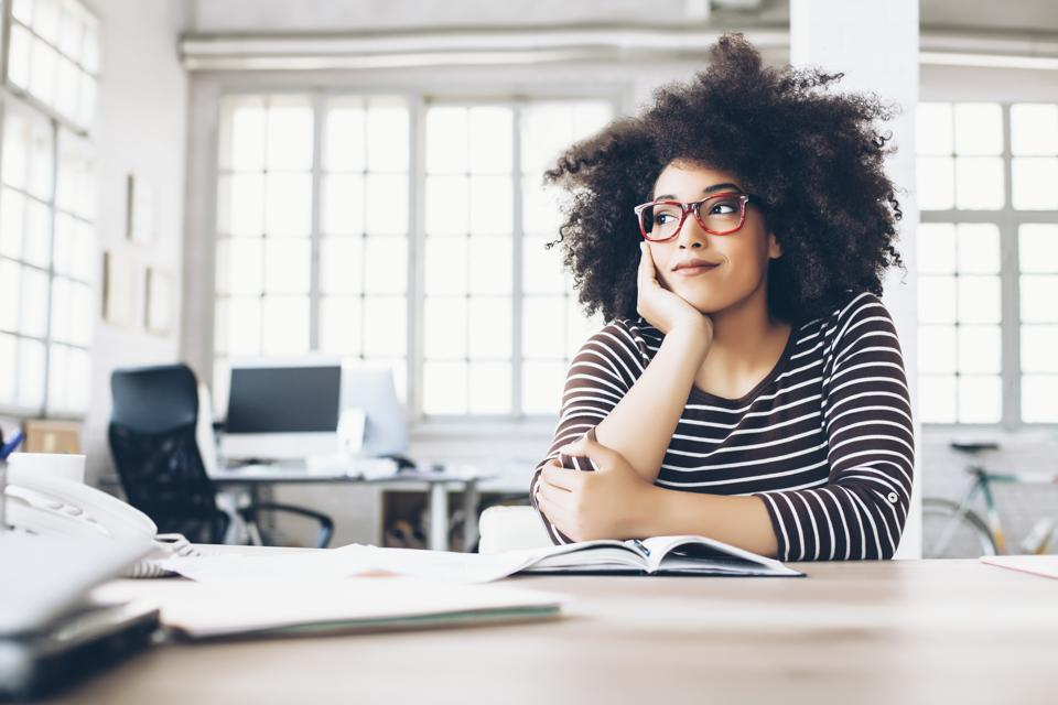 Pensive young businesswoman sitting on desk
