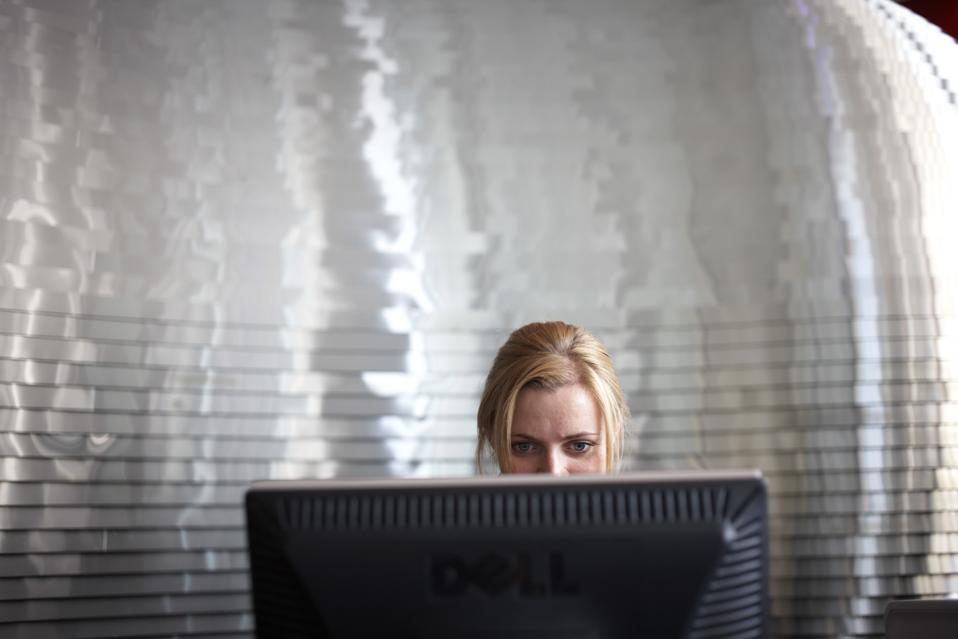 Kvinna som sitter vid en dator
