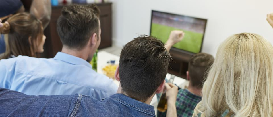 Fans of soccer watching match on tv screen