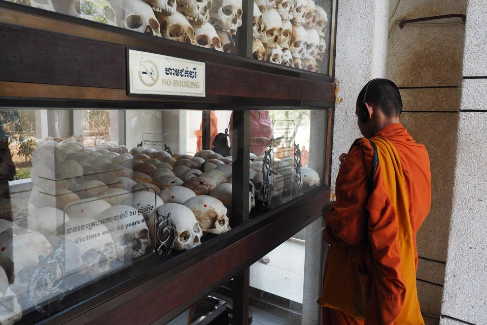 A Cambodian monk looks at a glass case of skulls, the remains of victims of Pol Pot and the Khmer Rouge