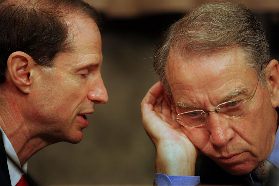 Senator Ron Wyden (D-OR) (L) speaks with Senate Finance Committee chairman Charles Grassley (R-IA). The two are co-sponsors of a bipartisan bill that would prevent $1,200 stimulus checks from being garnished by private debt collectors.