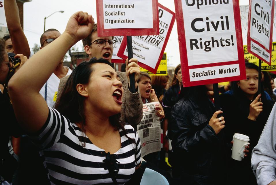 nuoret ihmiset, joilla on merkkejä sosialismista ja kansalaisoikeuksista, huutavat