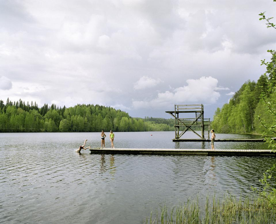 children swimming in a lake and diving from dock
