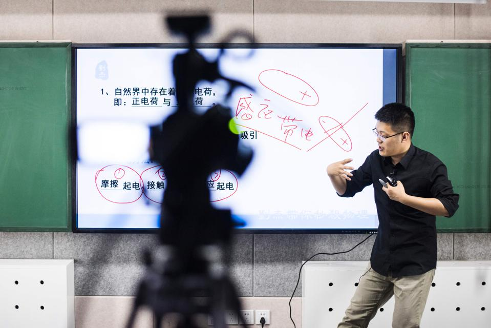 A Chinese high school teacher in front of a camera giving an online lesson
