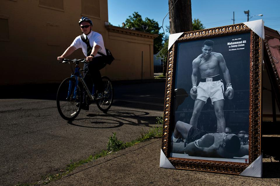 A Mormon missionary bicycles past the framed iconic photograph of Muhammad Ali standing before fallen opponent Sonny Listen. / AFP / Brendan Smialowski (Photo credit should read BRENDAN SMIALOWSKI/AFP/Getty Images)