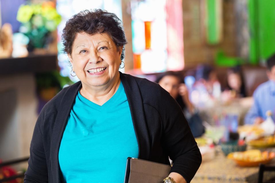 Senior Hispanic woman standing in her family owned restaurant