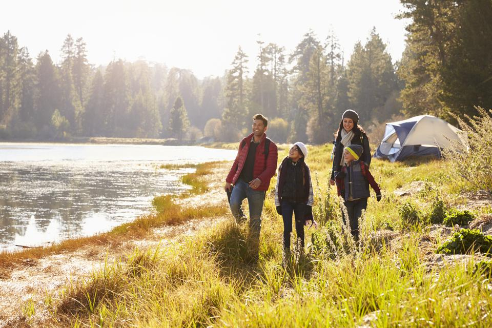Parents and two children on camping trip walking near