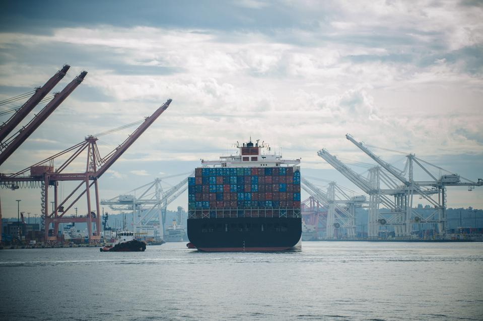 Tugboat and container ship in industrial harbor