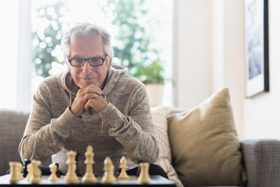 USA, New Jersey, Senior man sitting in living room and playing chess
