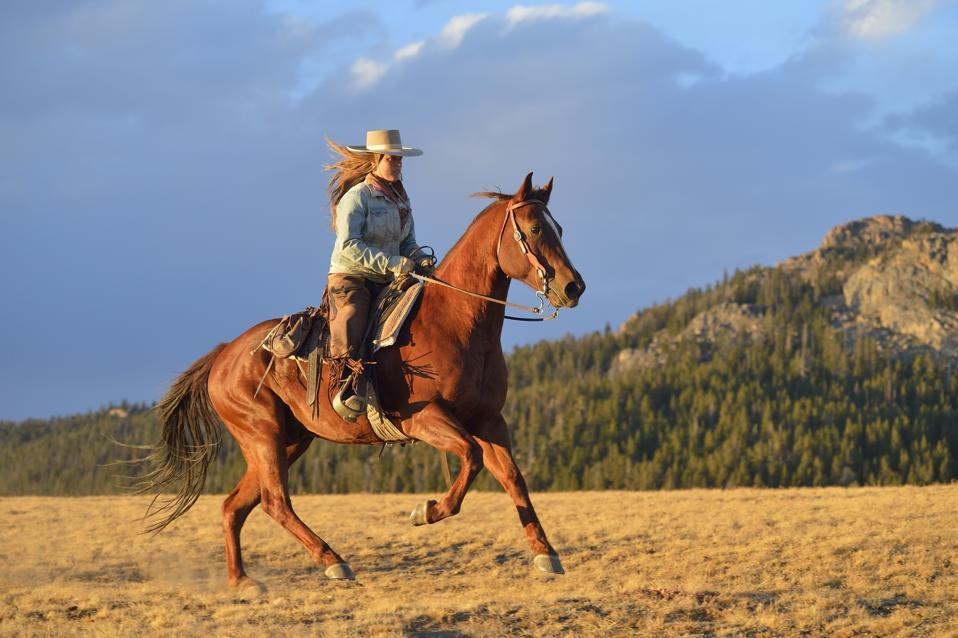 USA, Wyoming, riding cowgirl