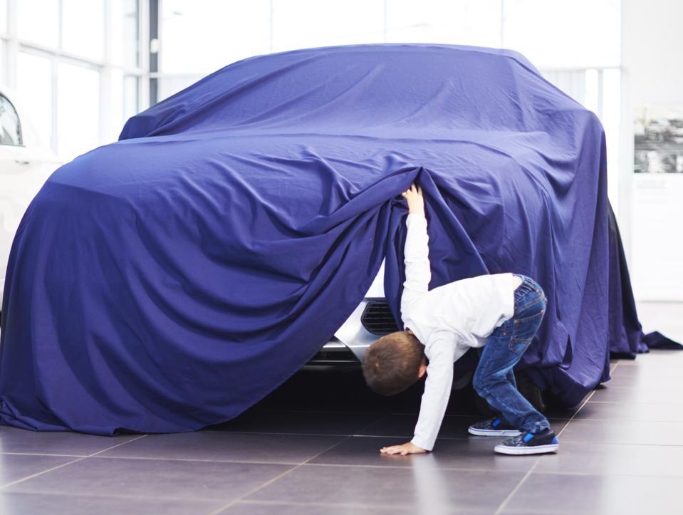 Boy at car dealer unveiling tarpaulin