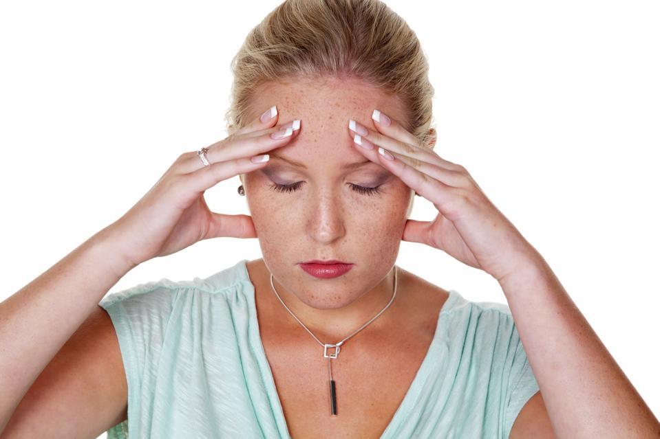 Eine junge Frau mit Migräne und Kopfschmerzen. Isoliert vor weißem Hintergrund
