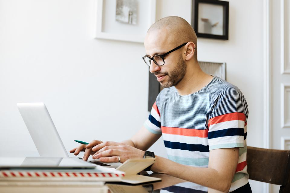 Bald Man Working On Laptop At Home