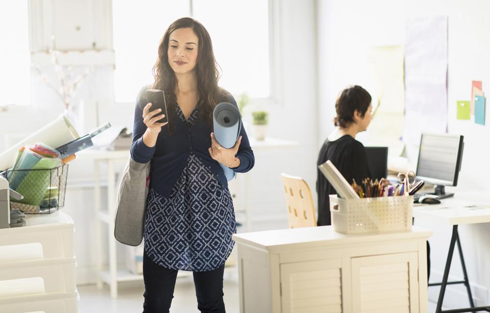 Businesswoman carrying yoga mat and cell phone in office