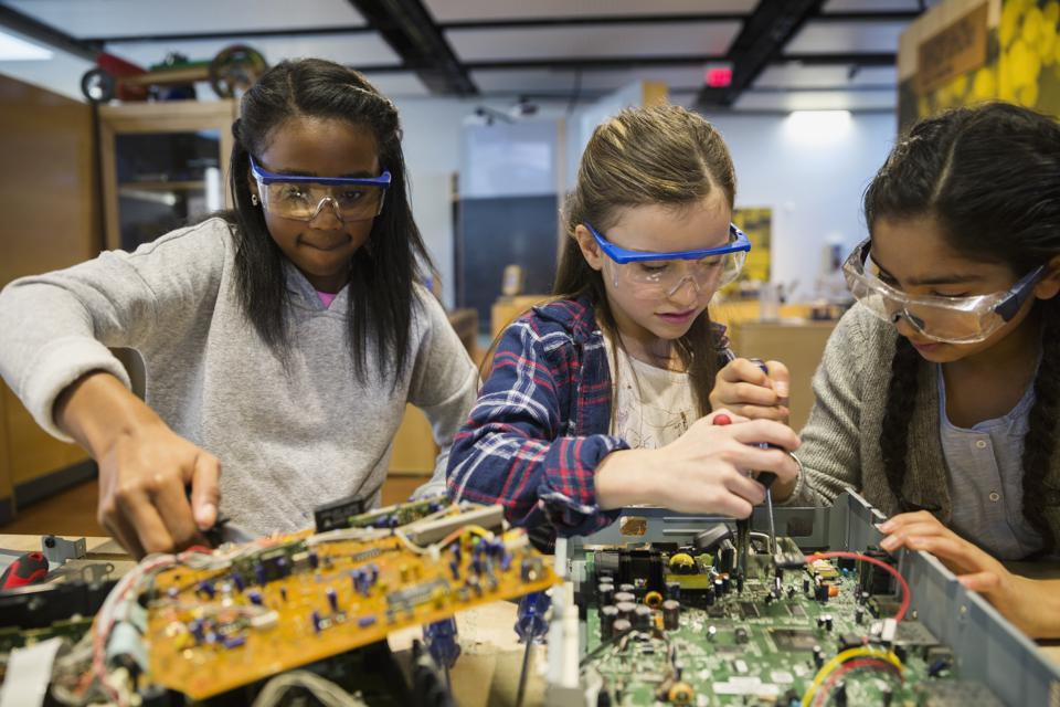 Students in goggles assembling electronics at science center