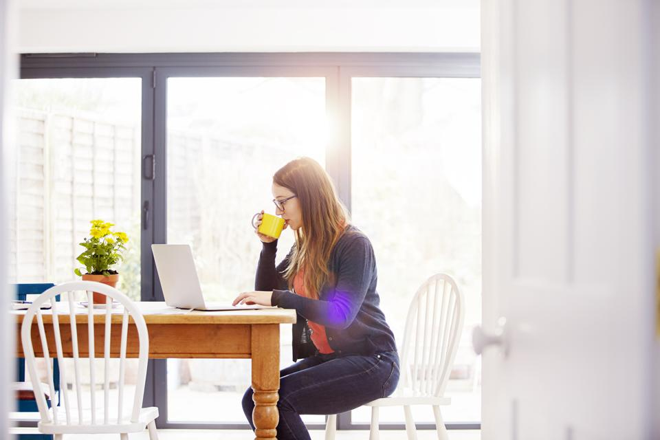 Girl working on laptop drinking coffee at home