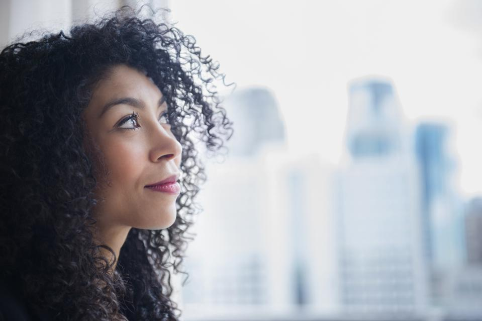 Mixed race businesswoman looking out window