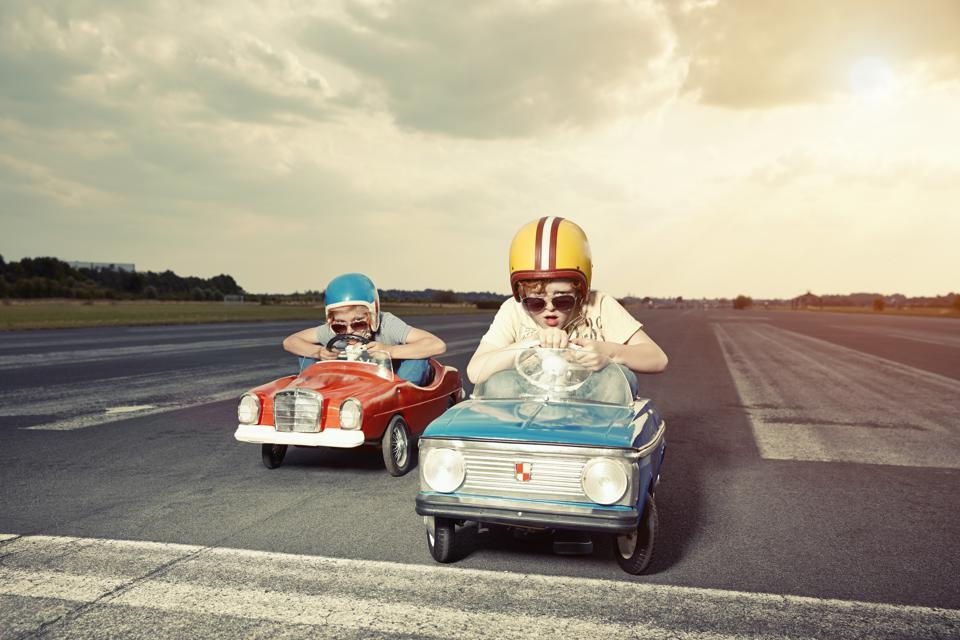 Two boys in pedal cars crossing finishing line on race track