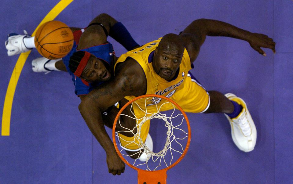 Laker center Shaquille O'Neal and Detroit Pistons' center Ben Wallace battle for a rebound in the fi