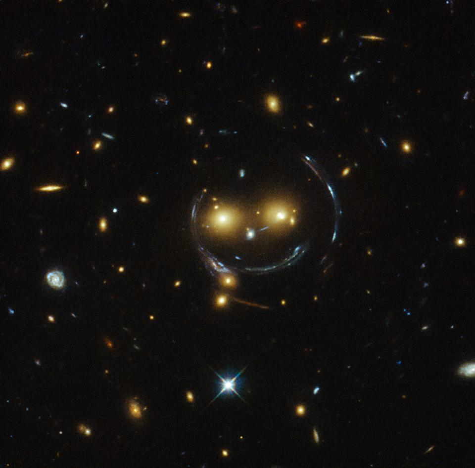 A chance alignment of foreground and background galaxies makes a smiley face.