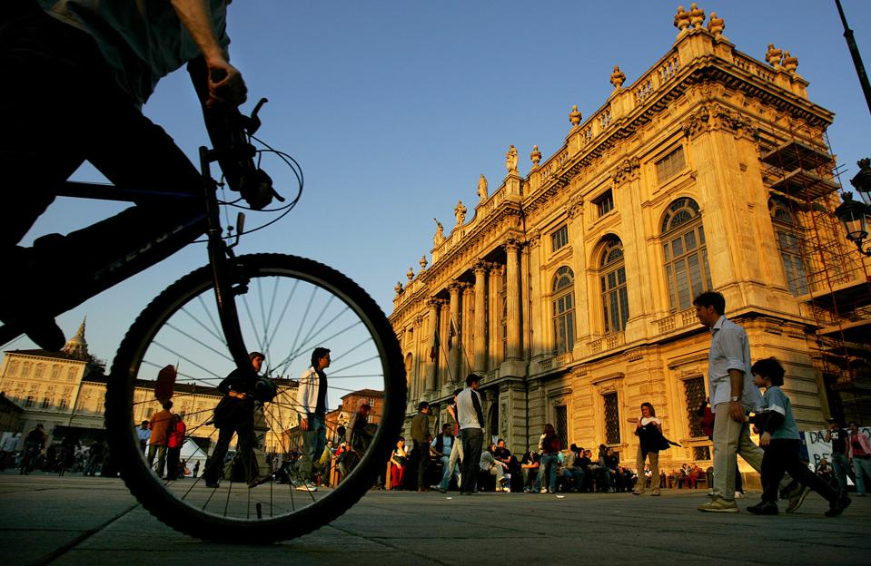 On a beautiful day in Turin, Italy people walk in front of the Palazzo Madama as the sun sets.