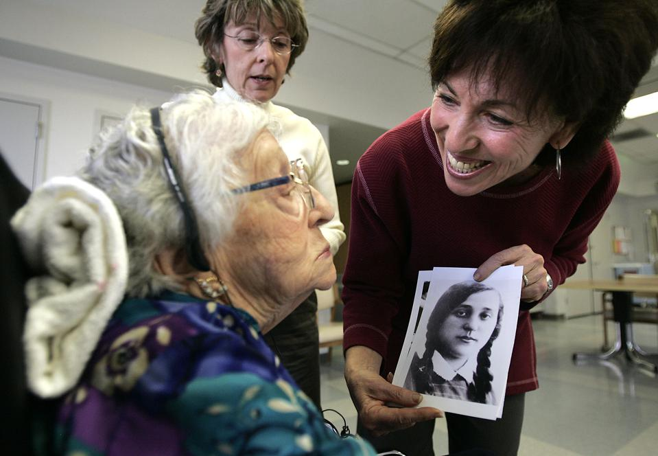 Esther Meyers, right, shows a photograph of her then–teenage mother Rachel Kane to her to jog her m