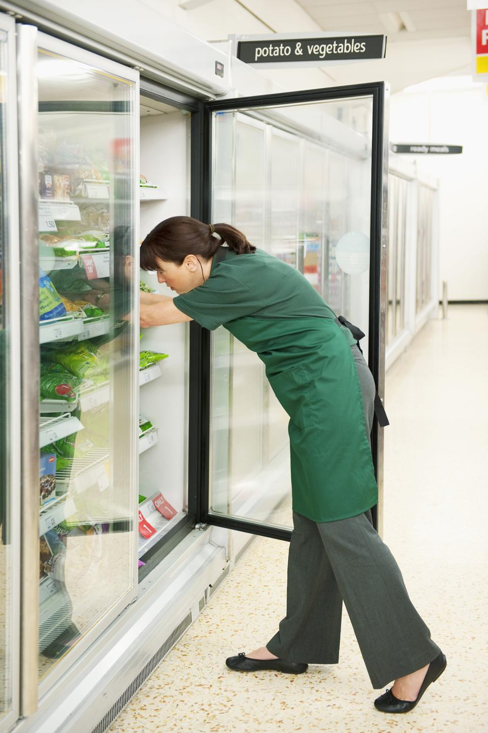 Caucasian worker checking stock in grocery store freezer