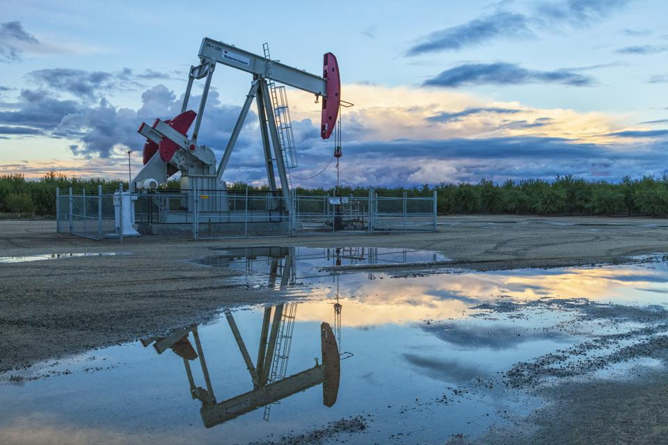 A pump jack and surface water at oil well and fracking site in Shafter