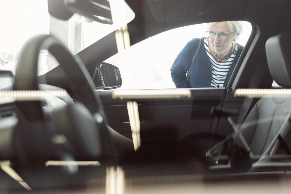 Senior woman admiring car displayed in store