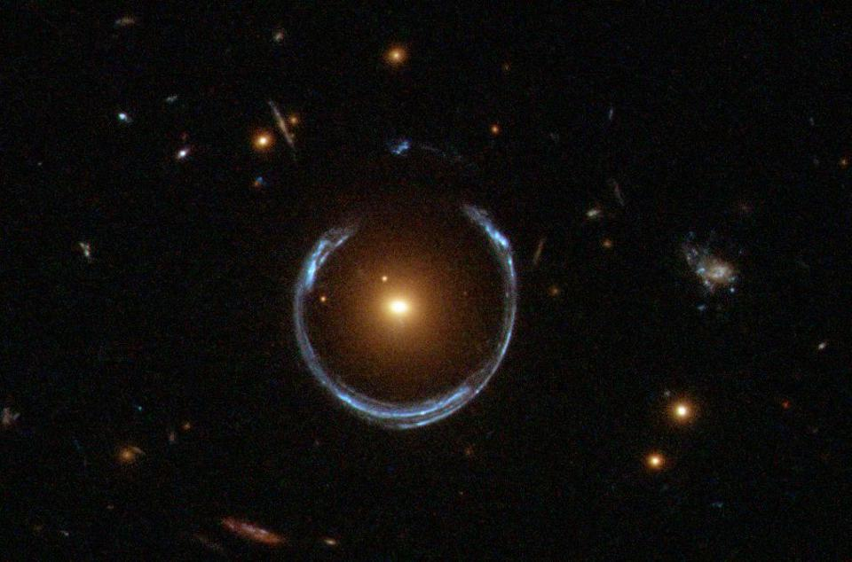 A horseshoe-shaped Einstein ring, just short of the perfect alignment needed for a ring.