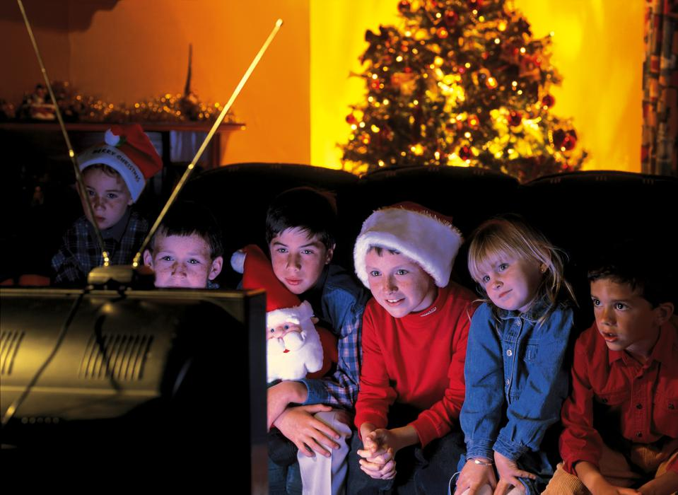 group of children watching television with a Christmas tree behind them